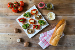 Bruschetta with beans and arugula, mushrooms, goat cheese. On a wooden board royalty free stock photography