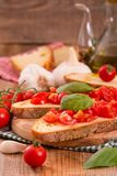 Bruschetta bread with basil and chopped tomatoes. Royalty Free Stock Photos