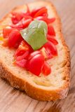 Bruschetta bread with basil and chopped tomatoes. Royalty Free Stock Image