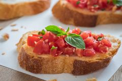 Bruschetta bread with chopped tomato and basil on paper Stock Photos