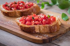 Bruschetta bread with chopped tomato and basil on wooden plate Royalty Free Stock Image