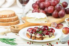 Bruschetta of Camembert or brie cheese with red grapes, rosemary and balsamic. Crostini. Gourmet wine snacks for foodies. Italian antipasti. Selective focus stock images