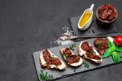 Bruschetta with Canned Sundried or dried tomato halves on stone serving board. Bruschetta with Canned Sundried or dried tomato halves and cream cheese on stone Stock Photos
