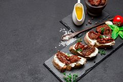 Bruschetta with Canned Sundried or dried tomato halves on stone serving board. Bruschetta with Canned Sundried or dried tomato halves and cream cheese on stone Royalty Free Stock Image