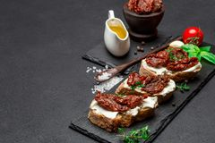 Bruschetta with Canned Sundried or dried tomato halves on stone serving board. Bruschetta with Canned Sundried or dried tomato halves and cream cheese on stone Royalty Free Stock Photos