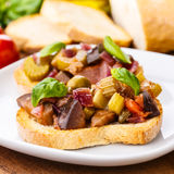 Bruschetta caponata. Fresh ciabatta bread with a tasty homemade caponata stock photo