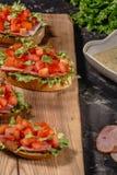 Bruschetta caseiro italiano com tomates, as folhas da salada, o presunto e molho desbastados no pão duro grelhado Vista horizont imagens de stock royalty free