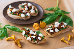 Bruschetta with chanterelle mushrooms, ricotta and basil Stock Photo