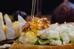 Bruschetta with cheese, fruit and nuts is drizzled with honey. royalty free stock photography