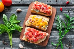 Bruschetta with cheese red and yellow tomatoes. The composition is decorated with leaves of basil, arugula, pepper and vegetables. Top view on an old wooden royalty free stock photos
