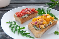 Bruschetta with cheese red yellow tomatoes and arugula. Bruschetta with cheese red and yellow tomatoes on a white plate. The composition is decorated with leaves stock photography