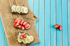 Bruschetta with cheese ricotta, strawberry and banana on wooden background Stock Image