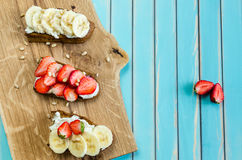 Bruschetta with cheese ricotta, strawberry and banana on wooden background Stock Photography