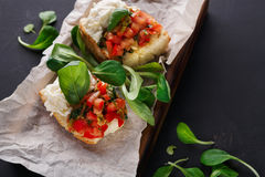 Bruschetta with cheese and vegetables on black background Royalty Free Stock Photos