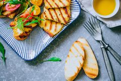 Bruschetta with cherry tomato salad with grilled haloumi cheese, with chard and arugula royalty free stock image