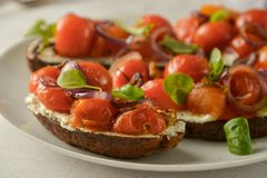 Bruschetta with cherry tomatoes and cheese cream. Healthy, vegan food, snack. Bruschetta with cherry tomatoes and cheese cream. Healthy, vegan food, bright stock photo