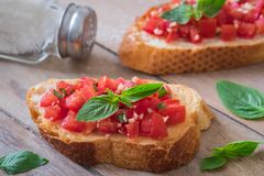 Bruschetta with chopped tomato and basil on toast and salt shaker Stock Images