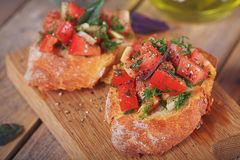 Bruschetta with chopped tomatoes, basil and herbs on grilled cru. Italian bruschetta with chopped tomatoes, basil, herbs and olive oil on grilled crusty bread Royalty Free Stock Images