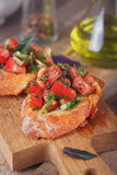 Bruschetta with chopped tomatoes, basil and herbs on grilled cru. Italian bruschetta with chopped tomatoes, basil, herbs and olive oil on grilled crusty bread Royalty Free Stock Photos
