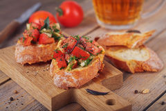 Bruschetta with chopped tomatoes, basil and herbs on grilled cru. Italian bruschetta with chopped tomatoes, basil, herbs and olive oil on grilled crusty bread Stock Images