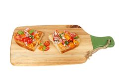 Bruschetta on a chopping board. Red onion and tomato bruschetta on a paddle shaped chopping board isolated against white Stock Photo