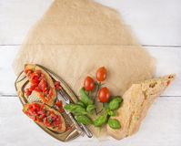 Bruschetta with ciabatta, tomatoes and basil on paper Stock Photos