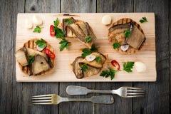Bruschetta com beringela posta de conserva com pimentões, alho e salsa em um suporte de madeira Fotos de Stock Royalty Free