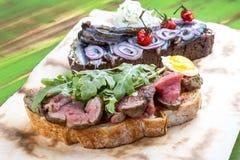 Bruschetta com carne assada e arenque pequeno fotografia de stock