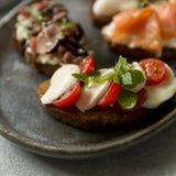 Bruschetta com mussarela e tomates e manjericão fotografia de stock