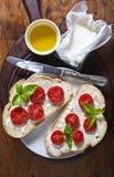 Bruschetta com os tomates de queijo macio, de manjericão e de cereja em uma madeira fotografia de stock