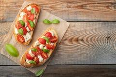 Bruschetta com tomates, mozzarella e manjericão em uma tabela rústica velha Aperitivo ou petisco italiano tradicional, antipasto  foto de stock royalty free