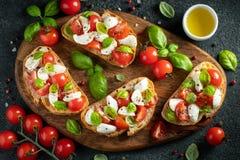 Bruschetta com tomates, mozzarella e manjeric?o em uma placa de corte Aperitivo ou petisco italiano tradicional, antipasto alto imagem de stock royalty free