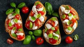 Bruschetta com tomates, mozzarella e manjeric?o em uma placa de corte Aperitivo ou petisco italiano tradicional, antipasto alto imagens de stock
