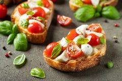 Bruschetta com tomates, mozzarella e manjeric?o em uma tabela r?stica velha Aperitivo ou petisco italiano tradicional, antipasto foto de stock royalty free
