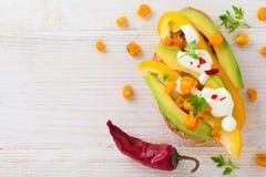Bruschetta con el aguacate, pimienta amarilla, granos de la pimienta del maíz, del perejil y de chile en un fondo de madera liger Foto de archivo