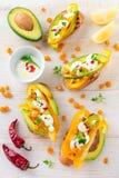 Bruschetta con el aguacate, pimienta amarilla, granos de la pimienta del maíz, del perejil y de chile en un fondo de madera liger Imagen de archivo libre de regalías