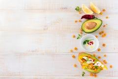 Bruschetta con el aguacate, pimienta amarilla, granos de la pimienta del maíz, del perejil y de chile en un fondo de madera liger Imagen de archivo