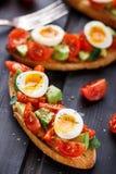 Bruschetta con el huevo del tomate, del aguacate y de codornices Imagen de archivo libre de regalías
