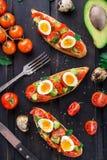 Bruschetta con el huevo del tomate, del aguacate y de codornices Foto de archivo
