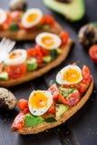 Bruschetta con el huevo del tomate, del aguacate y de codornices Fotos de archivo libres de regalías