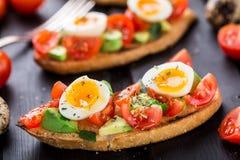 Bruschetta con el huevo del tomate, del aguacate y de codornices Fotografía de archivo