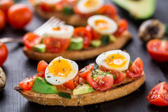 Bruschetta con el huevo del tomate, del aguacate y de codornices Foto de archivo libre de regalías