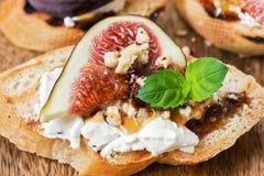 Bruschetta con el queso de cabra, los higos, las nueces y la miel, foco selectivo Primer italiano del aperitivo imagen de archivo
