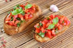 Bruschetta con el tomate, el ajo y la albahaca Imagenes de archivo