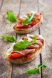 Bruschetta con i peperoni, il prosciutto di Parma e la rucola arrostiti Immagini Stock