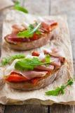 Bruschetta con i peperoni, il prosciutto di Parma e la rucola arrostiti Fotografie Stock