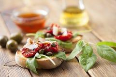 Bruschetta con i pomodori ed il razzo seccati al sole Fotografia Stock