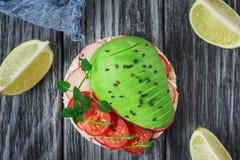 Bruschetta con il pomodoro, l'avocado, le erbe e la rucola Priorità bassa rustica Vista superiore fotografia stock libera da diritti