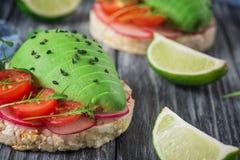 Bruschetta con il pomodoro, l'avocado, le erbe e la rucola Priorità bassa rustica Vista superiore immagine stock