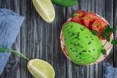 Bruschetta con il pomodoro, l'avocado, le erbe e la rucola Priorità bassa rustica Vista superiore immagini stock libere da diritti